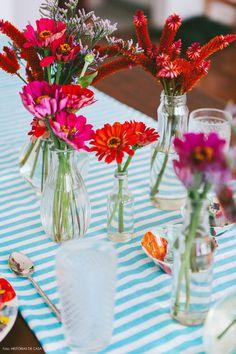 o que você vai precisar para copiar esse arranjo são flores coloridas de espécies variadas e diversas garrafinhas e potinhos de vidro transparentes, desses que todo mundo têm em casa, sabe? Podem ser embalagens de refrigerante, palmito, cilindros de vidro e até taças.Ou seja, não adianta inventar