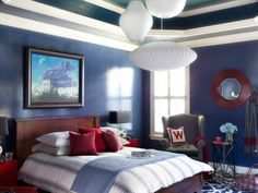 Prior to the makeover, this master bedroom was in contractor-grade condition, from its neutral carpet to the beige paint on its walls. Taking inspiration from its colorful abstract art, the room received a new identity with shades of blue accented with fire-engine red.