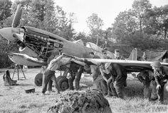Men of an RAF Repair and Salvage Unit working on a damaged Supermarine Spitfire Mk IX of 403 Sqn, RCAF, at a forward airstrip in Normandy.