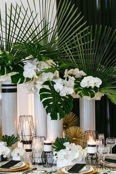 Gorgeous arrangements of white orchids and monstera leaves