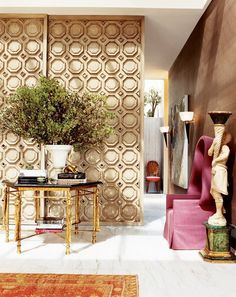 Eclectic entryway with pink chair and gold table