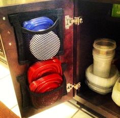 StorageWebs - Tupperware Lid Organizer. Amazing product! My husband makes these storage webs for our plastic lids because he was tired of the avalanche every time we opened the cabinet door! They work great and are breathable so if they aren't fully dry from the dishwasher. Click to go to the etsy store and buy them!