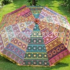A kaleidoscope of colour!  Will brighten up any setting, while it sparkles in the sunlight!  A wonderful modern styled indian garden parasol!
