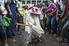 """A young Eyo masquerader dances as he leads the group into the Tafawa Balewa Square in Lagos on May 20, 2017. The white-clad Eyo masquerades represent the spirits of the dead and are referred to in Yoruba as """"agogoro Eyo"""". The origins of the Eyo Festival are found in the inner workings of the secret societies of Lagos where the masquerades ensure safe passage for the spirit of Kings and notable Chiefs into the afterlife. / AFP PHOTO / STEFAN HEUNIS"""