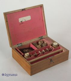 18th century inlaid maple fitted sewing box decorated with a hand colored print depicting Autumn Circa 1790.  The inside is lined in its original pink paper and has compartments for thread and ribbons.     There are two turned canisters which are in the shape of milk churns which have the upper part hollowed out to hold the thimble and thread waxer.