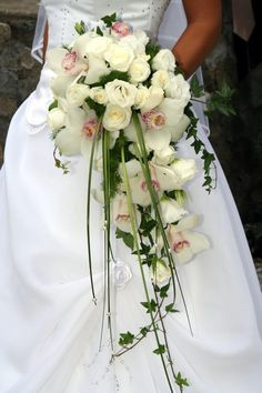 Cascading Cascade bouquets feature that descend below the main portion of the bouquet design. The voluptuousness of the bouquet is often the main feature of the wedding costume. Cascade bouquets are most often used in formal and traditional . Cascading Wedding Bouquets, Cascade Bouquet, Bride Bouquets, Bridal Flowers, Floral Wedding, Exotic Wedding, Wedding White, Bouquet Wedding, Orchid Bouquet
