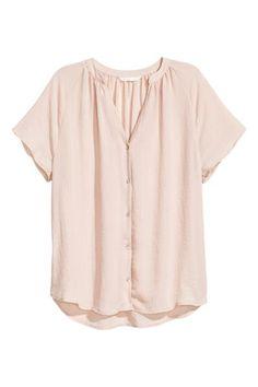 Blusa de mangas curtas em tecido. Modelo de corte folgado com pequena gola subida, decote em V e botões na frente. Base arredondada e ligeiramente mais comp