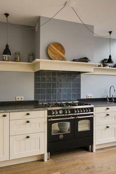 Landelijke keuken met fornuis en schouw. Voorzien van blauwe tegelachterwand en licht gestucte wand. Dit is mooi wonen in landelijke stijl.. Bekijk meer foto's op onze website! #landelijk #keuken #landelijkekeuken #landelijkestijl #landelijkwonen #schouw #landelijkeuitstraling #landelijkeschouw #fornuis