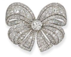 A DIAMOND BOW PENDANT/BROOCH   Designed as a pavé-set diamond double bow set with a circular-cut diamond weighing 4.56 carats, circa 1955, 6.0 cm wide, with French assay mark for platinum