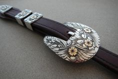 3/4'' sterling silver buckle set with 14 k gold flowers .