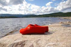 Snoogas tøfler i rød ved innsjøen.