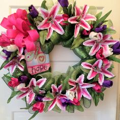 """Springing Forward"" is approx 27 inches. Made with two shades of green deco mesh with pink, purple, & white tulips, white/pink lillies, pink bow, and butterfly w/'Hope' wood signage. (CHECK OUT MY FB PAGE: Empire Wreath Co if interested in getting one of my creations!)"