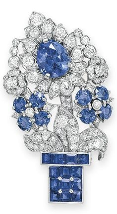 AN ART DECO DIAMOND AND SAPPHIRE BROOCH, BY CARTIER, CIRCA 1930. Designed as a square-cut sapphire vase, extending circular-cut sapphire and old-cut diamond blossoms and leaves, centring upon a pear-shaped sapphire, 2 1/16 ins., mounted in platinum, signed Cartier, numbered. #Cartier #ArtDeco