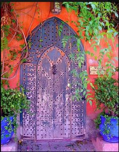 The unexpected wild purple color and coral facade around it makes it such a happy door to someone's Villa.