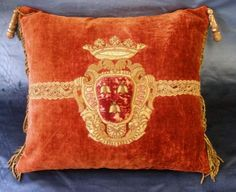 "18th Century Italian Coat of Arms Pillow. This coat of arms is possibly for Pope Urbanus VIII. Ornate crest thickly padded, shield with three bees facing up, embroidered in gold metallic threads on red silk velvet ground, mounted to antique velvet with 18th century trims, thick bullion fringe and gilt wood tassels at the top corners.  Wear appropriate with age. 23"" tall by 23"" wide."
