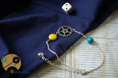 Très joli bracelet de cheville Rouage d'Eté, original et estival avec son engrenage et ses perles bleu marbré et jaune façon pastille, toutes deux de couleur très vives rappelant soleil et bord de mer.