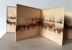 Alice Fox | Image of Rust Marks book #4. The rust print is made directly onto thick printmaking paper. The pages are then bound at each end of the concertina to form a book that can be explored page by page or as one long piece. The book measures 9.3 x 7.5 cm. It has 8 pages / sides (opening to approx. 70 cm when fully open). It comes with a little printed paper sleeve for when closed. Media: paper, tea, rust print.