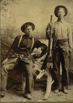 Imperial Size Photograph of Two Armed Cowboys ca 1890s - Two unidentified cowboys sitting in a studio with no identified photographer. This is a great image of two armed cowboys one with Winchester Rifle, the other sitting with holstered pistol and both wearing leather chaps, and cowboy hats. The man on the right has a small whip attached to his suspenders.