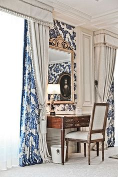 Beautiful blue and white draperies covered by a simple gray drapery with valance and tie backs.
