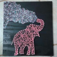 This wooden string/nail art elephant measures 12x12 inches. The background is black satin, the elephant is made with hot pink embroidery thread