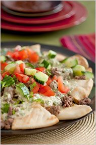 Greek Nachos-pita triangles toasted with olive oil; a sauce of feta and yogurt, spiked with mint and lemon; a topping of ground lamb with onion and cumin; and a garnish of tomatoes, cucumbers and olives.  Serve with a fresh fruit salad.