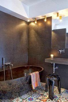 Design bagno moderno con il pavimento patchwork ed il rivestimento in piastrelle di mosaico nero - vasca autoportante nera