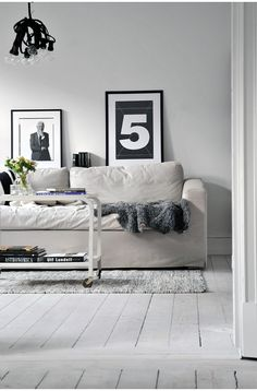 Shelf behind sofa to display blank & white photographs. White or black frames?