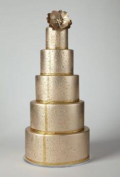 Multi-layered metallic gold cake with silver floral accents on top instead- looks so grand!