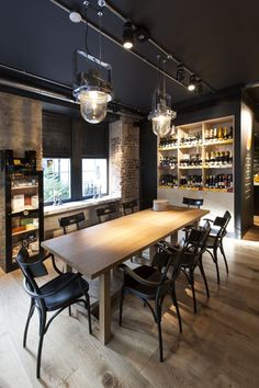 The New Street Wine Shop. Light is a central theme of this space, the dark ceiling and blinds limits its reflective capacity, forcing it into stark spotlights to draw the eye. The metal light fitting in the centre contrasts with the sleek wooden style of the rest of the room yet is subtle enough not to detract from the ambient design.