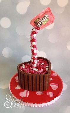 """Made for the family as we are all a fan of chocolate… Kit Kats and m&ms, 6"""" cake carved into heart shape on top of decorated board with striped heart cutouts. Second gravity cake using Lauren Kitchens gravity cake Craftsy Class (definiteLy..."""