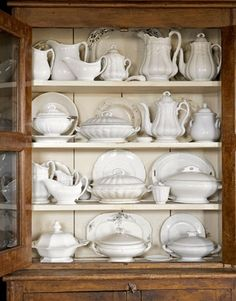 Farmhouse cupboard filled with white ironstone. Vintage perfection!