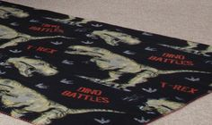 Dino Battles Fleece Blanket,  Matching room accessory for our Dino Battles collection adhorned with T Rex Dinosaurs and red wording TREX & DINO BATTLES.  Made from 100% Polyester Fleece Size 120x150cm  Other Matching accessories from this collection are available.  Not reccomended for under 3 years