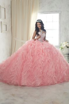 Make a lasting impression in a House of Wu Quinceanera Dress Style 26848 during your Sweet 15 party or any formal event. A ruffled ball gown pouring with iridescent organza and sparkle tulle, crowned