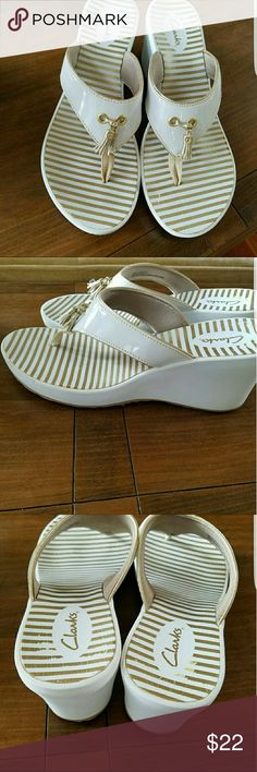 Clarks Sandals. EUC! White and gold with gold tassles. Love these! But not something I'd wear. Excellent used condition.   Open to offers.  Consider bundling.  30% off all bundle purchases! Clarks Shoes