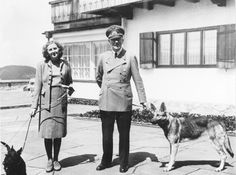 Hitler and Eva Braun at the Berghof. Hitler is holding Blondi, while Eva holds her dog, Negus.