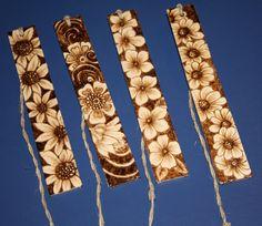 Marcadores de livros em madeira pirogravada, com motivos variados.