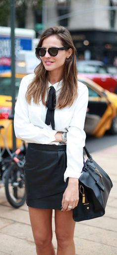 Silvia Zamora is wearing a leather mini skirt from Maje, white blouse with bow tie from IKKS and the bag is from Yves Saint Laurent