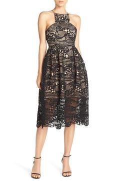 A high neckline and sharp cutaway shoulders take this playfully flared lace dress to a contemporary level.