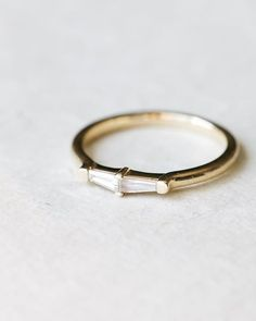 Easily one of our favorite designs - the Petite Tapered Baguette stacker.With an abundance of round gem shapes in jewelry, tapered baguettes stand out in sharp contrast in any stack (click the link to see it paired with other pieces) .Twin, .12ct TB's mirror one another on a minimalistic, polished band.Your own band is available online in Rose, White, and Yellow (featured) gold.Link in the BIO. PS - who likes the idea of this ring with even larger TBs?