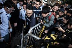Umbrella Revolution Hong Kong, A security staff member (C) removes a barricade outside the Citic tower near a protest site in the Admiralty district of Hong Kong on November 18, 2014. Security staff members assisted by Hong Kong bailiffs took action at pro-democracy barricades outside the building located near the main protest sites in the city, as pressure grows on demonstrators to leave. AFP PHOTO / Philippe Lopez (Photo credit should read PHILIPPE LOPEZ/AFP/Getty Images)