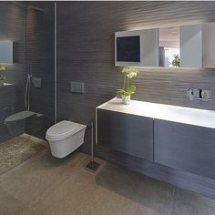 Timber textured wall, white in wall cistern unit, floating vanity with bench top basin, chrome tap and mixer. #taps #interiordesign #bathroom #australia #architecture #bathroomdesign #bathroomcollective Visit our website for more www.bathroomcollective.com.au