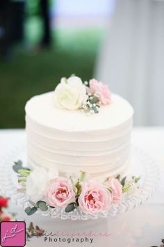 Small Wedding cake for the bride and groom, simple white layered cake with some of the wedding flowers for decoration.