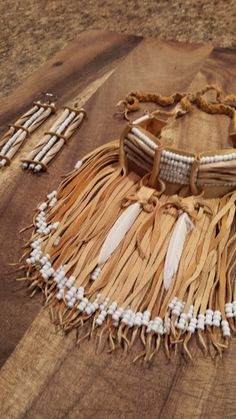 hand crafted buffalo bone beaded choker made into a deer hide piece with fringe. Embellished with feathers and various beads accompanied by matching bone beaded earrings