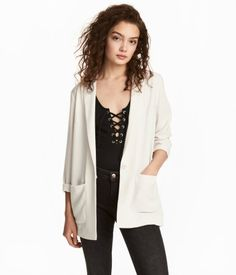 White. Single-breasted jacket in woven, crêped fabric. Notched lapels, pockets, and snap fastener at front. Unlined.