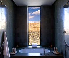 Amangiri, Utah    The Shower: The view plays an important role in the design throughout Amangiri, especially in the shower. At the end of a skylit dressing room in the 34 suites, a large wet room clad in green limestone is outfitted with a sunken tub, twin rain showers, and a floor-to-ceiling vertical picture window that frames the imposing mesa or the ample desert.