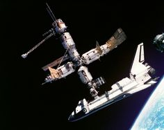 In this historical photo from the U.S. space agency, the Space Shuttle Atlantis, still connected to Russia's Mir Space Station, was photographed by the Mir-19 crew on July 4, 1995. Cosmonauts Anatoliy Y. Solovyev and Nikolai M. Budarin, Mir-19 Commander and Flight Engineer, respectively, temporarily undocked the Soyuz spacecraft from the cluster of Mir elements to perform a brief fly-around.