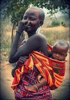 Africa | A Masai mother carrying her child