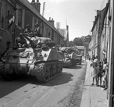 Sherman tanks of UK 30th Corps passing through Bayeaux France 17 June 1944.