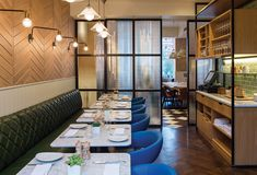 Hotel Indigo Kensington | restaurant design | banquettes with quilted leather | tongue and groove vertical paneling | chevron timber panels | calacatta oro marble | fluted glass screens
