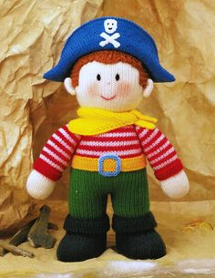 "Meet the Pirate from Jean Greenhowe's 'Storybook Dolls' collection. He looks like he's all set to help folk out rather than rob them, with that cheery expression. He is knitted with DK wool, is easy to make and is 31cm/12.25"" tall (excl. head decor). Designed and published by Jean Greenhowe Designs in 1996."